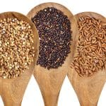 Three different types of seeds on wooden spoons.
